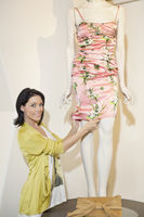 Portrait of a beautiful mid adult woman adjusting dress on mannequin in fashion boutique