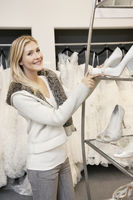 Portrait of a cheerful young woman standing by footwear standing in bridal store