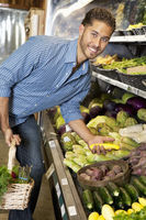 Portrait of a happy man shopping for vegetables in market