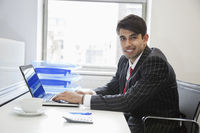 Portrait of an indian businessman writing on paper at desk in office