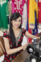 Portrait of an indian female dressmaker using sewing machine