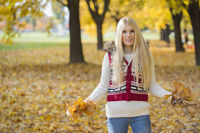 Portrait of beautiful young woman holding autumn leaves in park