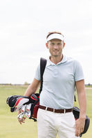 Popular : Portrait of confident man carrying golf club bag against clear sky