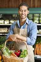 Portrait of handsome young salesperson standing with basket full of vegetables