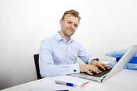 Portrait of happy businessman using laptop at desk in office