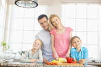Portrait of happy family preparing food in kitchen