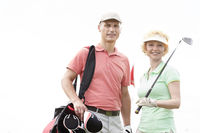 Popular : Portrait of happy male and female golfers standing against clear sky