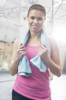 Popular : Portrait of happy woman with towel around neck standing in crossfit gym