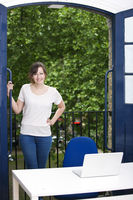 Portrait of happy young businesswoman standing by balcony with laptop on desk