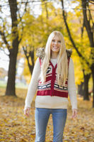 Portrait of happy young woman standing in park during autumn