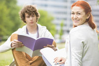 Portrait of happy young woman with male friend studying at college campus