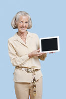 Portrait of senior woman showing tablet pc against blue background