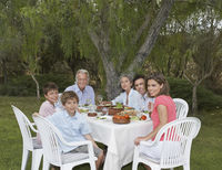 Portrait of three-generation family including children  6-11  at sitting garden table