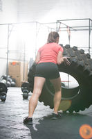 Rear view of woman flipping tire in gym