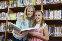 School girl and teacher holding book in library portrait