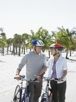 Senior couple on bicycles on tropical beach