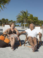 Senior couple on sunloungers on tropical beach holding hands