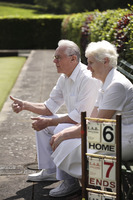 Popular : Senior couple sitting on a bench in a bowling green
