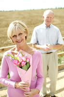 Popular : Senior woman holding a bouquet of flowers with her husband standing in the background