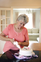 Senior woman putting icing on a cake