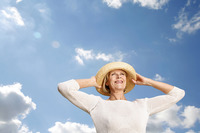 Popular : Senior woman smiling while holding her hat