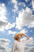 Senior woman with hat smiling while looking up