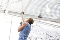 Popular : Side view of dedicated man climbing rope in crossfit gym