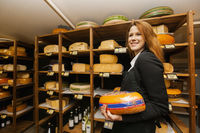 Side view of female salesperson holding cheese in store
