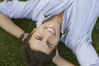 Smiling businessman lying down on grass