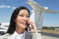 Smiling businesswoman standing outside airplane talking on mobile