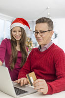 Smiling father and daughter shopping online at home during christmas