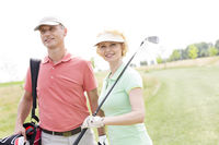 Popular : Smiling male and female friends standing at golf course