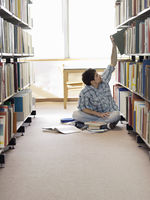 Student sitting on floor in library reaching for book