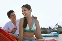 Popular : Teenage boy  16-17  applying sunscreen lotion to girl s back