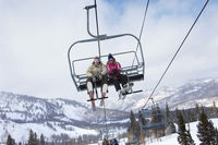 Teenage couple  16-19  wearing skis sitting on ski lift low angle view