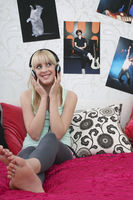 Popular : Teenage girl  16-17  sitting on bed listening to music