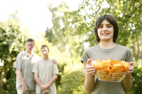 Teenage girl holding a bowl of chips with her father and brother standing in the background