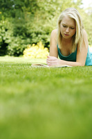 Teenage girl lying forward on the field reading book