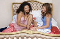 Popular : Teenage girl painting friend s fingernails on bed at slumber party