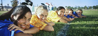 Popular : Teenage girls  13-16  lying in row on soccer field