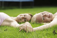 Teenage girls holding hands while lying on the field