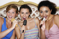 Teenage girls using brushes as microphones singing at  slumber party