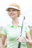 Popular : Thoughtful middle-aged woman looking away while holding golf club