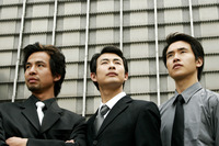Three businessmen standing in front of the building