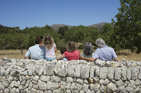 Three-generation family with two children  6-11  by stone wall back view
