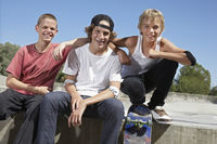 Popular : Three teenage boys  16-17  with skateboards at skate park portrait