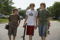 Popular : Three teenage brothers  13-17  walking on street carrying skateboards