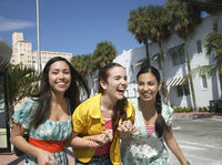 Popular : Three teenage girls  16-17  walking on street and laughing
