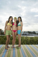 Popular : Three teenage girls  16-17  wearing bikinis standing on wooden deck portrait