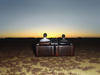 Two business people in arm chairs in open plain at sunset back view